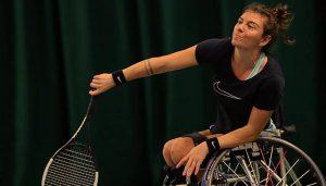 Lauren playing a shot while playing tennis